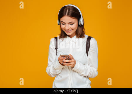 Portrait of a smiling teenage schoolgirl in uniform with headphones holding mobile phone isolated over orange background - Stock Photo