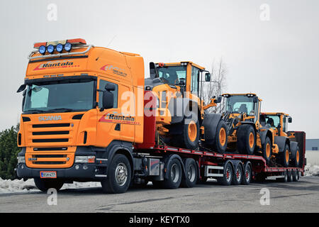 LIETO, FINLAND - MARCH 12, 2016: Scania R500 V8 truck is ready to haul three Volvo L60H wheel loaders. The operating - Stock Photo