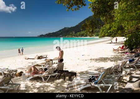 The Seychelles, Mahe, Beau Vallon, beach, tourists relaxing beside sea on sun loungers - Stock Photo