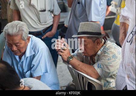 22.10.2017, Singapore, Republic of Singapore, Asia - Elderly men sit around a table at a public square adjacent - Stock Photo