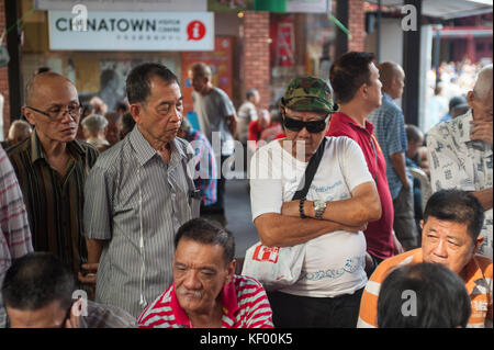 22.10.2017, Singapore, Republic of Singapore, Asia - Elderly men stand around a table at a public square adjacent - Stock Photo