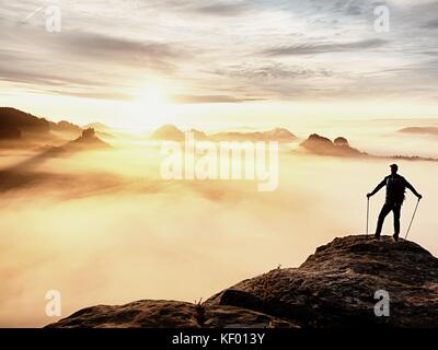 Man silhouette with poles in hand. Sunny spring daybreak and tourist guide stay on sharp cliff of mountain. Hiker - Stock Photo