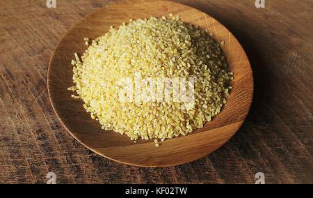 Dry bulgur wheat in wooden bowl isolated Spilled bulgur - Stock Photo