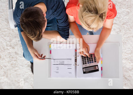Couple Using Calculator For Calculating Invoice, Tax, Bills And Retirement Money On Desk At Home - Stock Photo