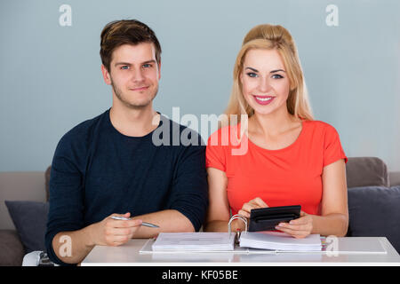 Smiling Couple Calculating Invoice Using Calculator To Plan Family Budget And Save Money At Home - Stock Photo