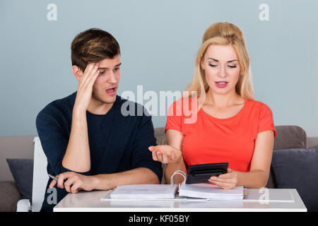 Worried Couple In Finance Debt Calculating Their Money And Bills On Desk At Home - Stock Photo
