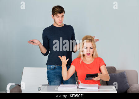 Shocked Young Couple Looking At Bills And Budget And No Money Left At Home - Stock Photo