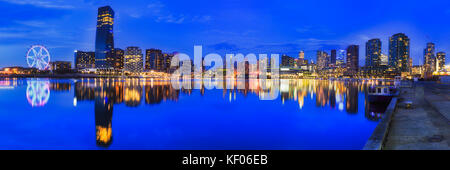 Melbourne docklands suburb with modern high-rise towers at sunset relecting in Yarra river. - Stock Photo