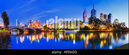 Blur colourful sunrise over Melbourne city CBD with bright downtown lights reflecting in still waters of Yarra and - Stock Photo