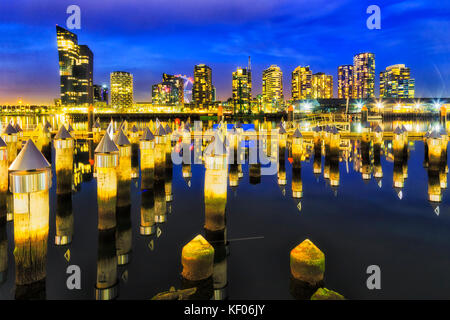 Matrix of timber jetty poles pinning out of still waters of Yarra river at Melbourne's docklands marina and suburb - Stock Photo