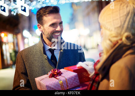 Man surprising woman with unexpected gifts - Stock Photo