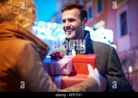 Mature man receiving full of presents from  woman - Stock Photo