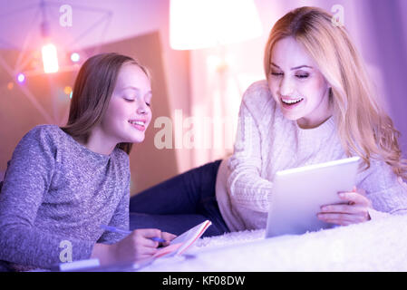 Happy mum showing something on the tablet to her daughter - Stock Photo