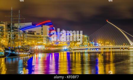 Dublin, Ireland, night view of Samuel Beckett Bridge over Liffey River and Jeanie Johnston Tall Ship. - Stock Photo