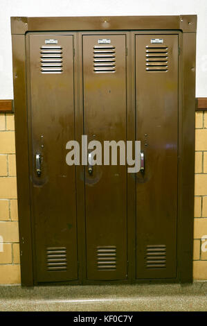 Three solid steel, wall mounted storage cupboard lockers in a vertical portrait orientated image. - Stock Photo