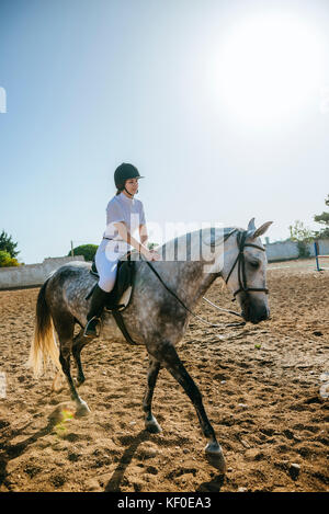 Young woman riding on horse - Stock Photo