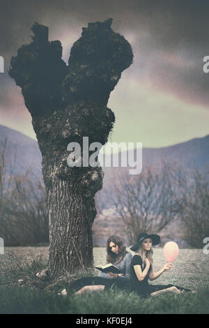 Opposites: two girls sitting under a tree, one holding a pink balloon, the other holding a book - Stock Photo