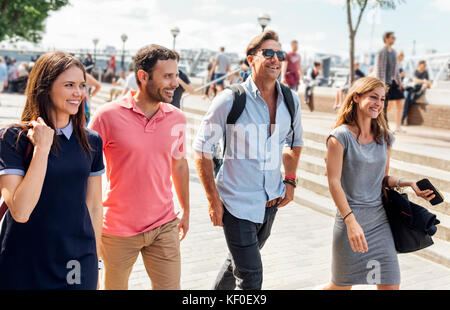 UK, London, group of friends walking along the banks of the Thames River - Stock Photo