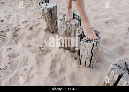 Woman's feet walking on wooden stakes on the beach - Stock Photo