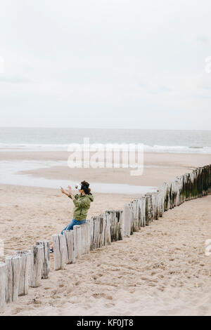 Woman sitting on wooden stake on the beach wearing VR glasses - Stock Photo