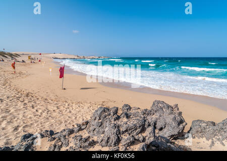 view of the beach with some rocks and red flags, Parque Natural de las Dunas de Corralejo, Fuerteventura, Canary - Stock Photo