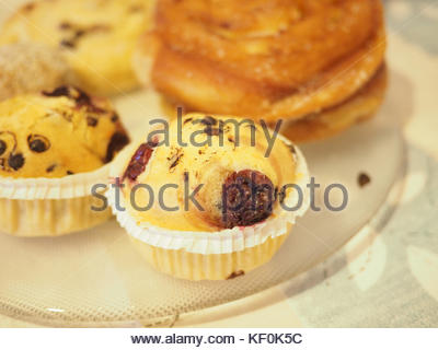 Close up of chocolate vanilla muffins on a plate in soft focus - Stock Photo