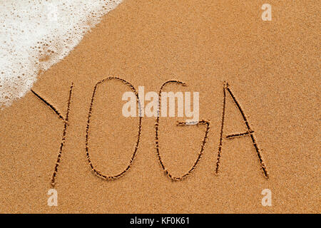 the word yoga written in the sand of a beach, with sea foam in a corner - Stock Photo