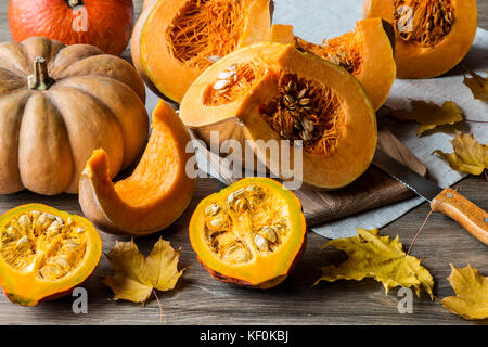 Sliced pumpkin with seeds on a wooden background. Close-up - Stock Photo