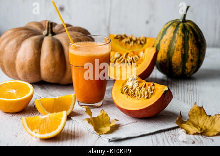 pumpkin fresh juice with ingredients on white wooden background. detox healthy drink - Stock Photo