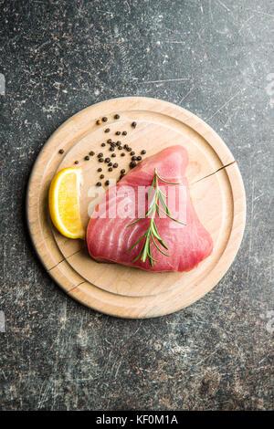 Fresh raw tuna steak on cutting board. - Stock Photo