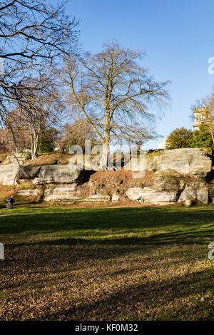 Autumnal leaves on oak trees on Tunbridge Wells Common an artist caryying a portfolio case passes sunlit rocks, - Stock Photo
