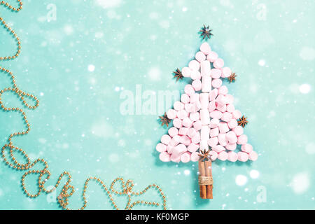 Fir tree silhouette from pink marshmallows on blue background. Christmas concept, New year holiday winter - Stock Photo