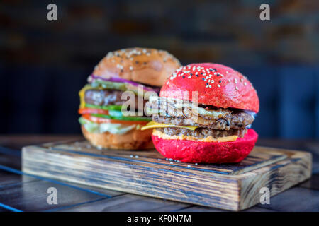 Two different restaurant burgers on wooden board - Stock Photo