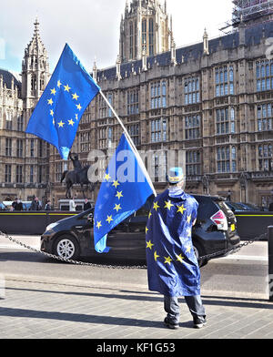 London, UK. 25th October, 2017. A lone anti-Brexit protester waves two European Flags outside the Houses of Parliament, - Stock Photo