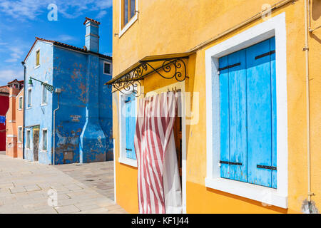 VENICE ITALY VENICE Fishermans houses Yellow or blue painted house with wooden door blue shutters Island of Burano - Stock Photo