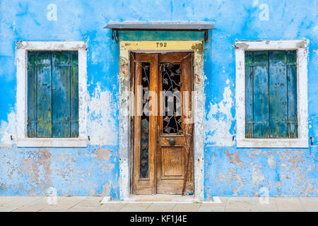 VENICE ITALY VENICE Fishermans house Shabby blue painted house with wooden door and blue shutters Island of Burano - Stock Photo
