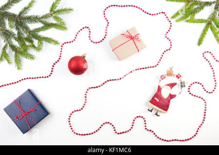 Christmas composition. Fir tree branch, small gifts and Xmas decoration on white background - Stock Photo