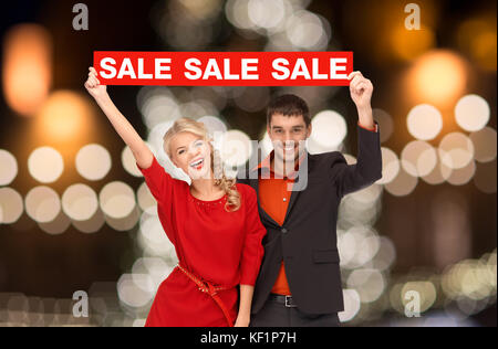 couple with red sale sign over christmas lights - Stock Photo