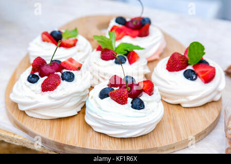 Sweet cakes with fresh berries lying on the wooden dish - Stock Photo