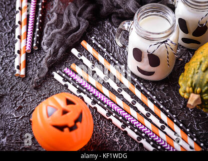 Colorful festive striped paper straws and Halloween decor - Stock Photo