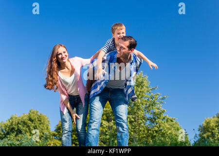 Daddy carrying son piggyback on his back  - Stock Photo