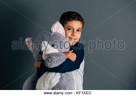 Adorable boy hugging his teddy bear on gray background - Stock Photo