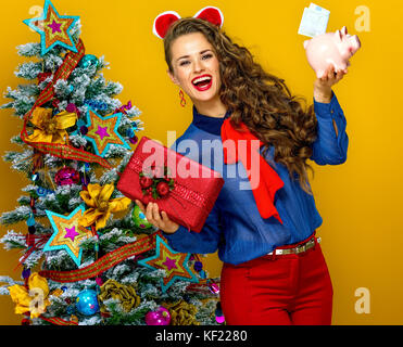 Festive season. happy young woman near Christmas tree on yellow background showing present box and piggy bank with - Stock Photo