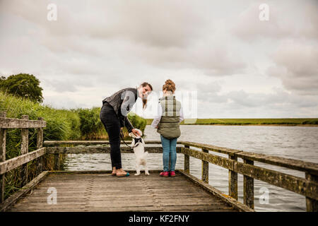 Mother and daughter standing on jetty at a lake with dog - Stock Photo