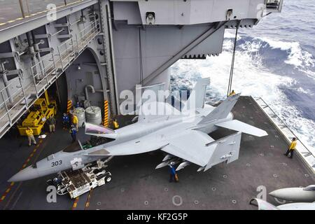 U.S. Navy sailors move a F/A-18E Super Hornet jet fighter aircraft onto an aircraft elevator aboard the U.S. Navy - Stock Photo