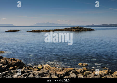 Sunny summer view across the sea from the Scottish West Highland coast at Mallaig with rocks, blue sky and the distant - Stock Photo