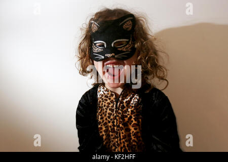A young 5-year-old girl pictured dressed up as a cat for Halloween fun and celebrations in Chichester, West Sussex, - Stock Photo