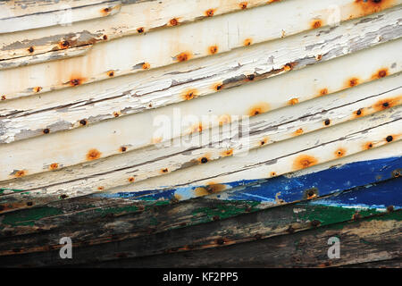 Peeled paint on weathered rusting wooden boards on boat ship hull side - Stock Photo
