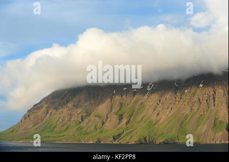 Cloud cover over mountain top and blue skies in Siglufjordur, North Iceland, Scandinavia - Stock Photo