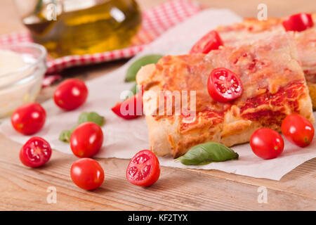 Italian pizza with cheese, tomatoes and fresh basil. - Stock Photo